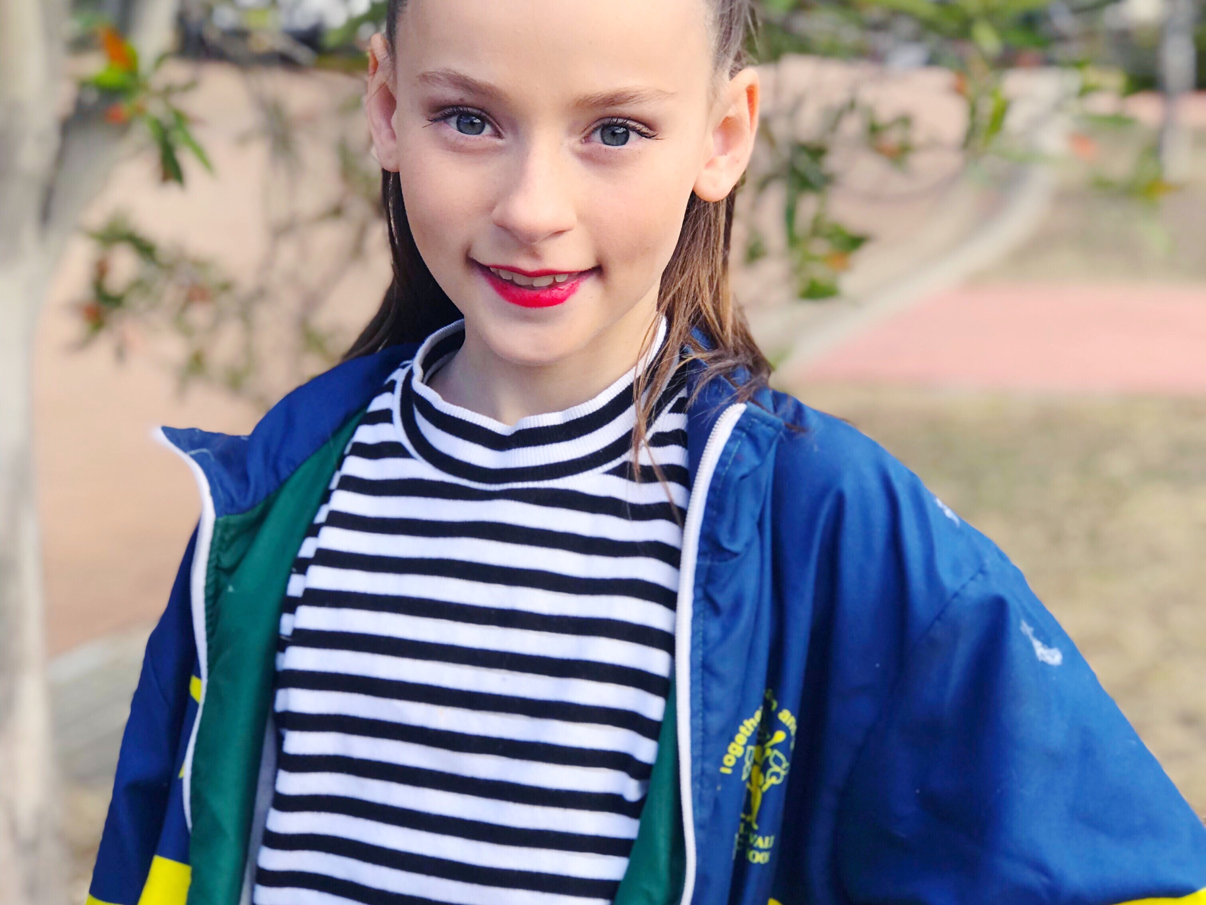 Girl with pony tail smiling in front of tree in dance clothes