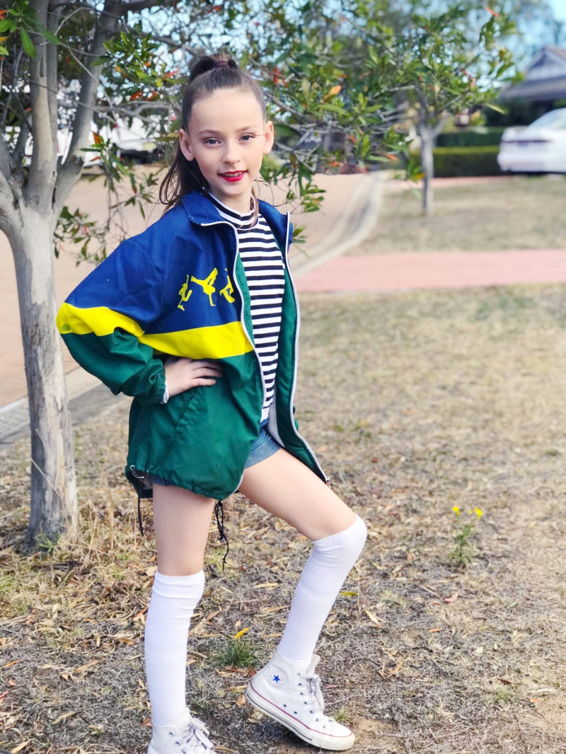 Girl in front of tree in knee high socks and knee bent