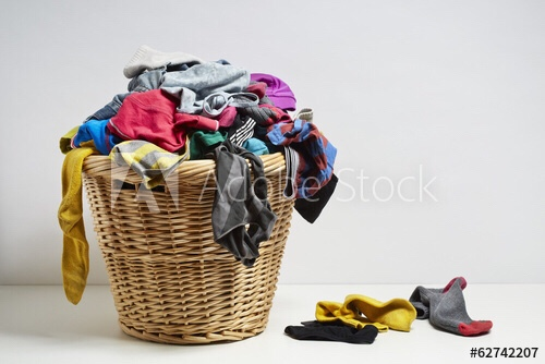 Cane washing basket with clothes in it and clothes on the floor yellow socks