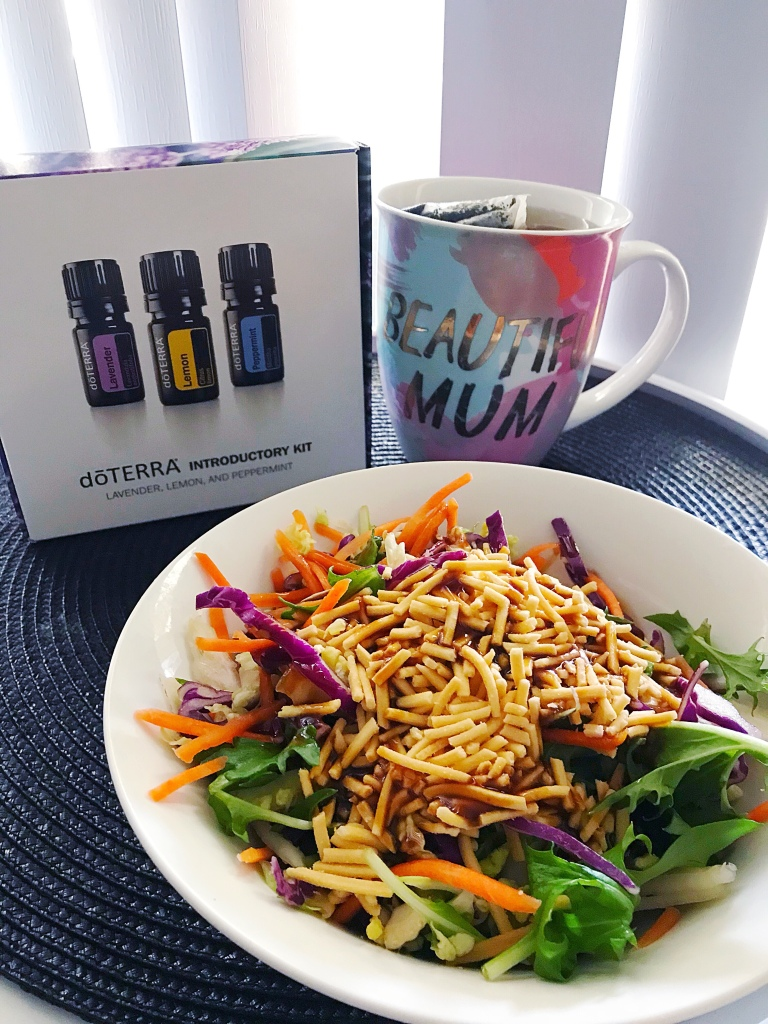 Lavender lemon peppermint essential oils tea cup Asian noodle salad on round table
