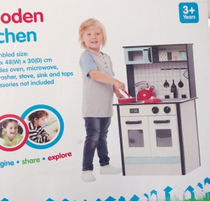 Kmart kitchen box with blonde child laughing, wooden kitchen
