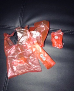 Red plastic bags with screws and nails on black pleather lounge