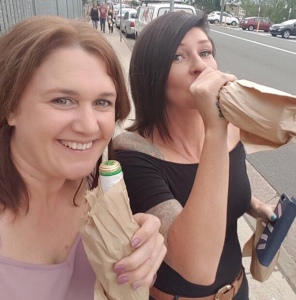 Woman in pink top smiling women with black hair drinking from bottle in brown paper bag