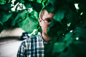 Man with glasses hiding behind green leaf