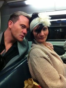 Blonde man and black haired woman with head band on a train with heads touching