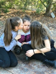 Girls in a park kissing a toddlers cheeks toddler frowning