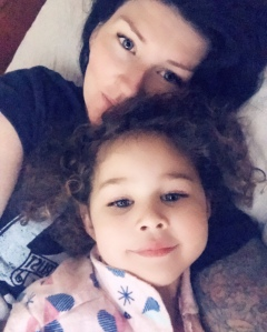 Woman and daughter laying in bed smiling