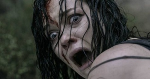Woman screaming and looking scared in a horror movie scene