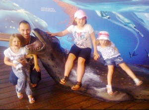 Father and three daughters at aquarium kneeling down sitting on a statue