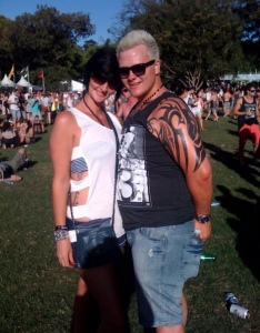 Blonde guy and black haired girl at festival, outside on grass