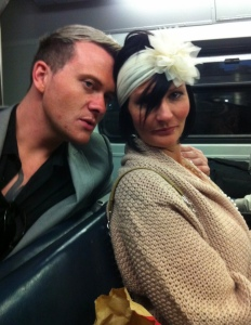 Blonde haired guy resting his head on black haired girls shoulder on a train in 1930's dress up