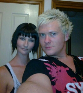 A man and woman taking a selfie, black bob hair and blonde spiked hair.