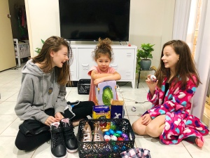 Three girls sitting on the floor with black boots, clothes and Cadbury Easter eggs. Girls smiling at each other