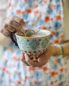 Lady holding a cup of tea stirring with a spoon. Floral dress